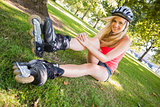Casual cheerful blonde wearing roller blades and helmet