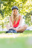 Casual smiling blonde wearing inline skates and helmet sitting