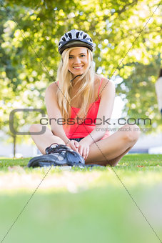 Casual smiling blonde wearing inline skates and helmet sitting