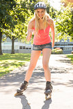 Casual smiling blonde inline skating