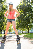 Casual cheerful blonde standing hands on hips wearing inline skates