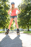 Casual smiling blonde standing hands on hips wearing inline skates