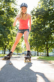 Casual smiling blonde inline skating on pathway