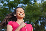 Joyful sporty woman jogging in a park