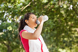 Sporty woman with towel on shoulders drinking water
