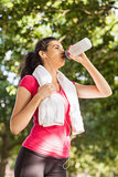 Cute sporty woman having a break and drinking water