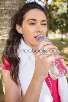 Beautiful sporty woman leaning against a tree