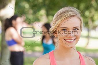 Beautiful blonde sporty woman posing in a park