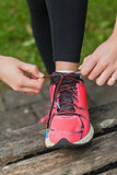 Close up of young woman tying her shoelaces