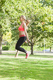 Side view of sporty woman skipping