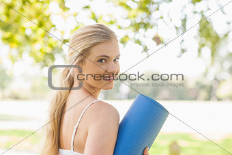 Beautiful sporty woman posing holding an exercise mat