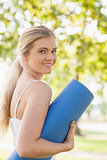 Gorgeous blonde woman posing holding an exercise mat