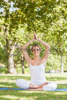 Cute young woman doing yoga sitting on an exercise mat