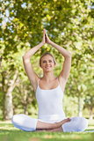 Cheerful smiling woman meditating with hands raised in prayer