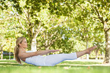 Side view of beautiful woman doing yoga in a park