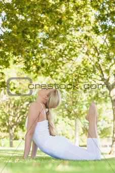 Beautiful young woman wearing white clothes doing yoga