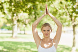 Pretty fit woman doing yoga in a park