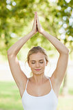 Front view of peaceful young woman doing yoga in a park