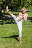 Young sporty woman practicing yoga standing on a lawn