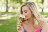 Side view of cute casual woman smelling a white flower
