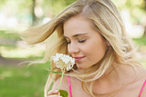 Gorgeous content woman smelling a flower with closed eyes