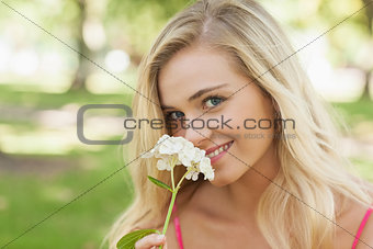Beautiful blonde woman smelling a flower sitting in a park