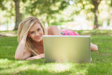 Beautiful blonde woman posing lying on a lawn