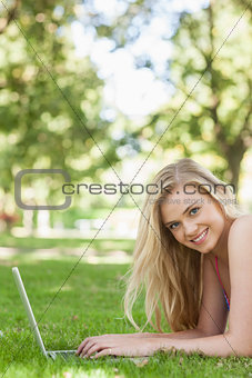 Portrait of cheerful young woman using her notebook lying on a lawn