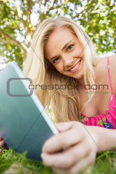 Calm attractive woman holding her tablet lying on a lawn