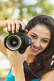Happy attractive woman holding her camera