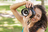 Cute brunette woman taking a picture with her camera