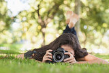 Young woman using her camera for taking a picture lying on a lawn