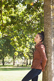 Attractive woman leaning against a tree with closed eyes
