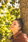 Side view of brunette woman leaning against a tree