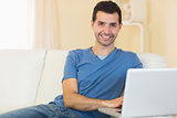 Casual smiling man sitting on couch using laptop