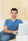 Casual cheerful man sitting on couch using laptop