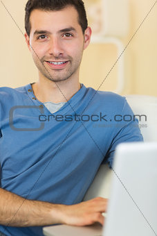 Casual happy man sitting on couch using laptop