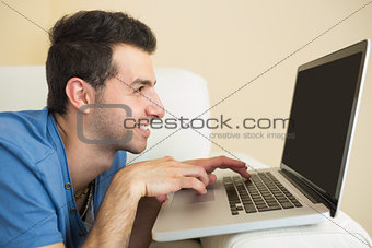 Casual smiling man sitting on couch using and looking at laptop