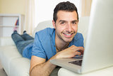 Casual cheerful man sitting on couch using laptop looking at camera
