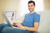 Casual content man sitting on couch using laptop looking at camera
