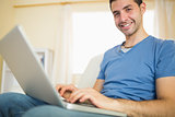 Casual attractive man sitting on couch using laptop looking at camera