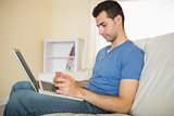 Casual calm man sitting on couch using looking at laptop