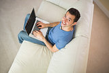 High angle view of casual smiling man using laptop