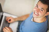 High angle view of casual cheerful man using laptop
