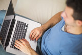 High angle view of casual man using laptop sitting on couch