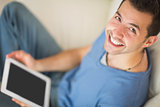 High angle view of casual smiling man using tablet sitting on couch