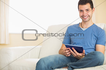 Casual smiling man using tablet sitting on couch