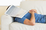 Casual man lying on couch with newspaper covering head