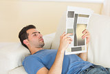 Casual calm man lying on couch reading newspaper