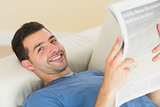 Casual smiling man lying on couch holding newspaper